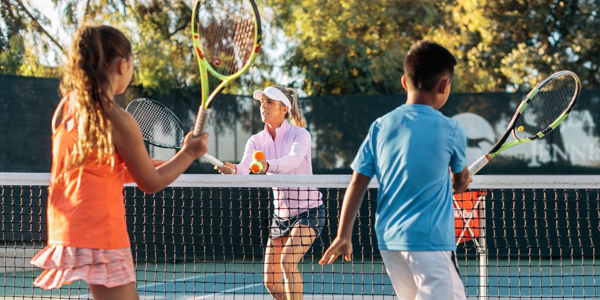 A coach teaching tennis to children.