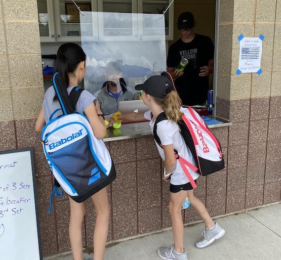 Los jugadores de tenis juveniles se registran para el campamento de verano en Dakota del Sur con el vidrio de seguridad en su lugar.
